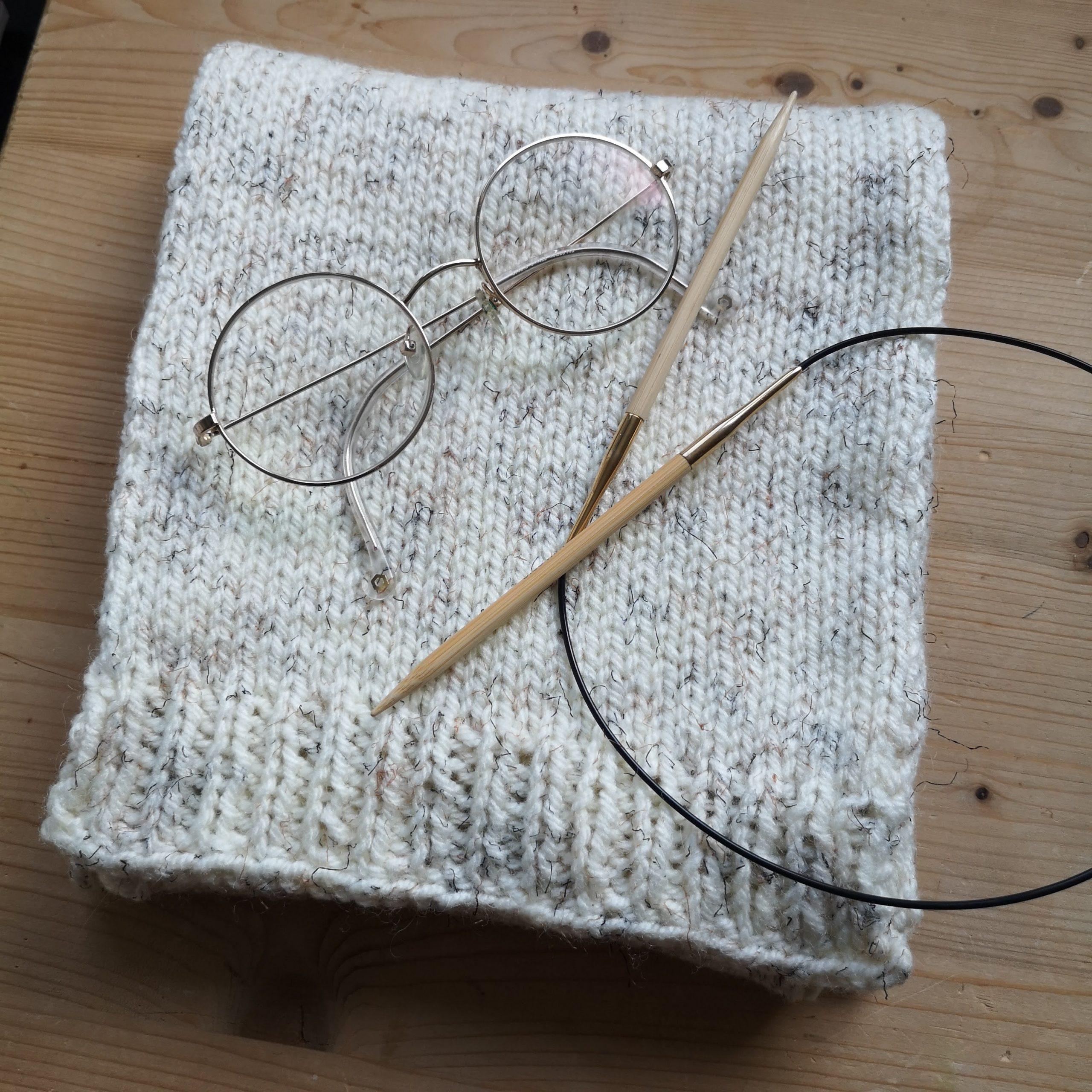 Netjes opgevouwen gebreide sjaal met een rondbrenaald en een bril erop gelegd voor de sier.